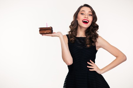 Cheerful charming retro styled young woman holding piece of chocolate birthday cake with candle on the palm over white background Imagens