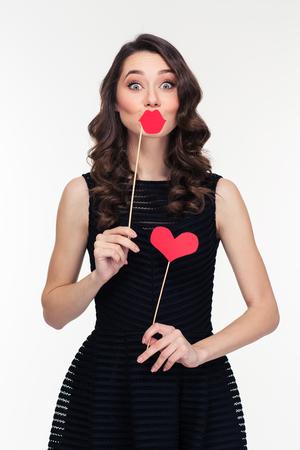 Grappig mooi krullend jonge vrouw met retro kapsel in zwarte jurk spelen met behulp van valse lippen en hart rekwisieten op stokken geïsoleerd op witte achtergrond