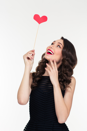 attractive women: Portrait of cheerful attractive curly retro styled young woman with heart booth isolated over white background
