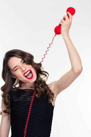 telephone cable: Amusing funny retro styled young curly woman imitating choking with telephone cable isolated over white background