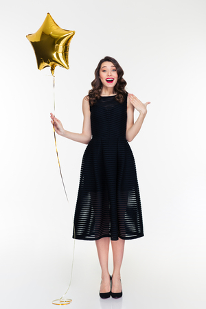 elated: Surprised elated curly retro styled young woman in black dress and shoes with golden star shaped balloon isolated over white background