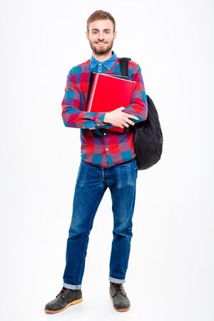 man studying: Full length portrait of a happy male student holding books standing isolated on a white background