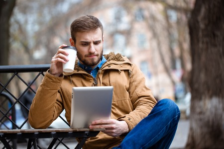 Handsome consentrated bearded young man in coat and jeans drinking coffee and using tablet in open air cafe