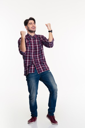 winner man: Full length portrait of a casual man celebrating his success isolated on a white background Stock Photo