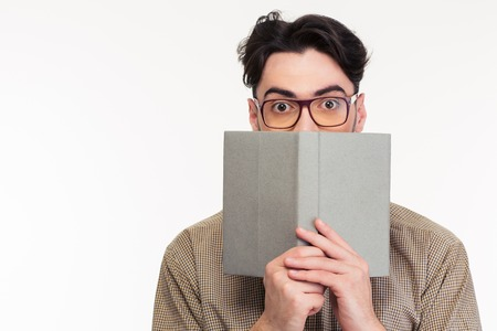 Portrait of a young man covering his face with book isolated on a white background