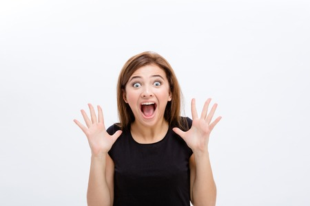 Doen schrikken schreeuwende jonge vrouw in zwarte top op witte achtergrond