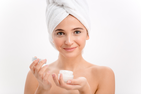 Beautiful young female with towel on her head using face cream over white background