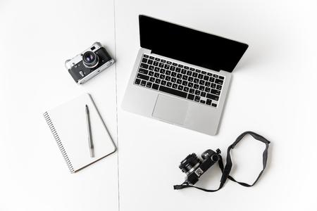 Bovenaanzicht van twee camera's, blocnote met pen en leeg scherm laptop geïsoleerd over witte achtergrond