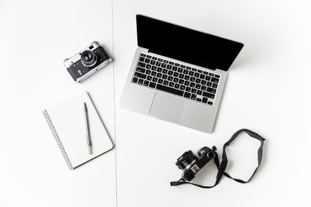 trompo de madera: Vista superior de dos cámaras, el bloc de notas con la pluma y el ordenador portátil de pantalla en blanco aislada sobre fondo blanco