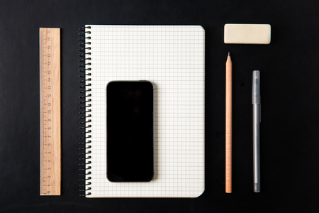 ball pens stationery: Top view of school supplies and blank screen mobile phone isolated over black background Foto de archivo
