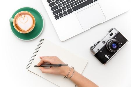 노트북의 상위 뷰, 오래 된 카메라, 흰색 배경 위에 노트북에 커피와 여자의 손 쓰기의 컵 스톡 콘텐츠