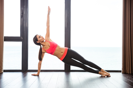 warm up exercise: Portrait of a sports woman doing yoga exercises in fitness gym Stock Photo