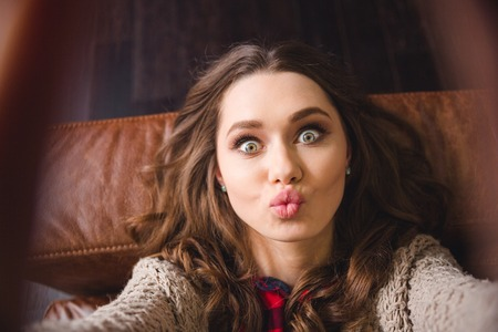 Retrato de una mujer joven tumbado en el sofá y que hace la foto autofoto mientras que los besos a la cámara Foto de archivo