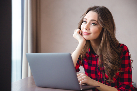 Portrait of a smiling pretty woman using laptop computer and looking at camera Stock Photo