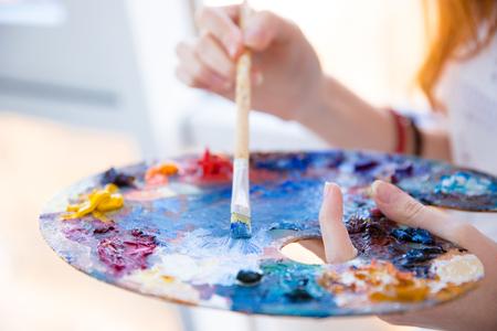 artistas: Primer plano de pincel en manos de la mujer en la paleta de mezclar pinturas