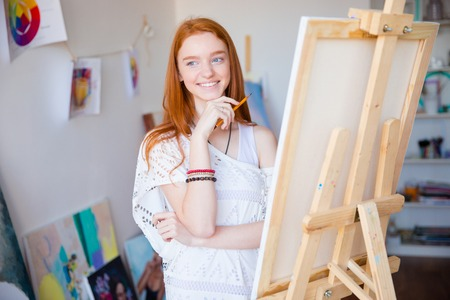 long red hair: Happy inspired smiling female artist with long red hair drawing with pencil in art class