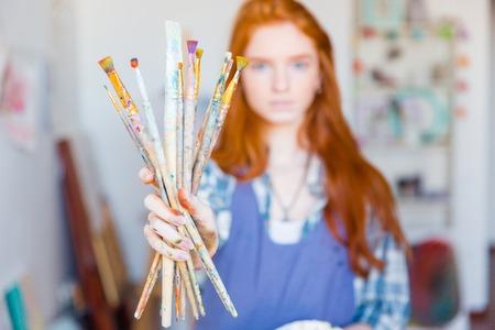 brocha de pintura: pintor de la mujer joven con el pelo largo de color rojo en el delantal azul que muestra sucios pinceles en el taller del artista Foto de archivo