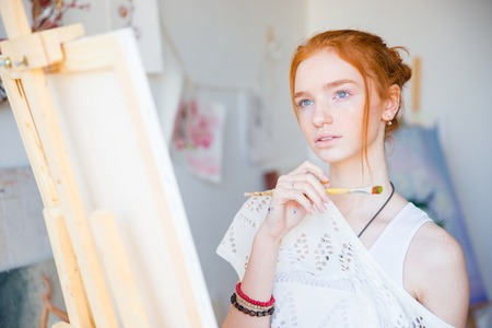 painter: Thoughtful attractive young woman painter standing in front of easel with paintbrush and dreaming in art workshop