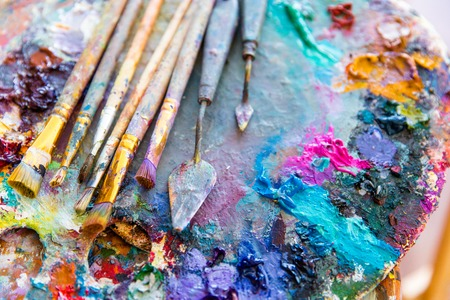 Background image of bright mixed color paints on art palette with paintbrushes and palette knives