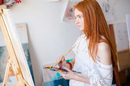artwork painting: Concentrated pensive young woman painter with long red hair painting on canvas using oil paints in art studio