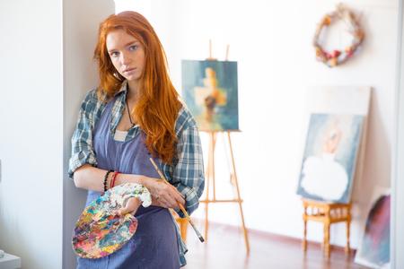 Doordachte aantrekkelijke jonge vrouw schilder met lang rood haar in schort met kunst palet en penseel in kunstenaar workshop