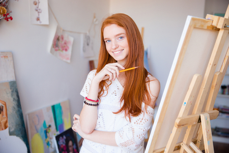 hair studio: Cheerful attractive young woman artist painter sketches by pencil in drawing class Stock Photo