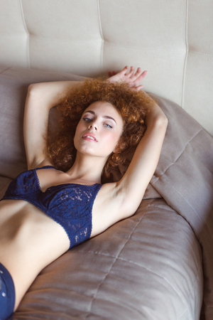 Sensual alluring curly young woman in lace bra lying on bed and relaxing