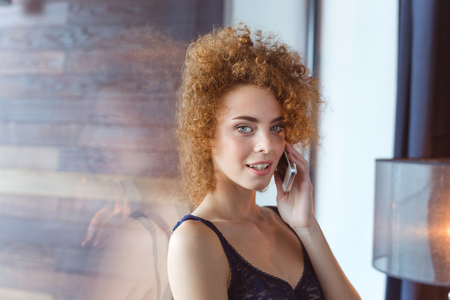 lace bra: Seductive relaxed young woman with curly red hair in lace bra  talking on mobile phone standing at the window Stock Photo