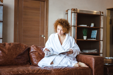female magazine: Charming relaxed redhead young female stting on leather sofa and reading fashion magazine