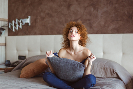 tempting: Tempting sensual curly redhead young woman sitting and resting on bed