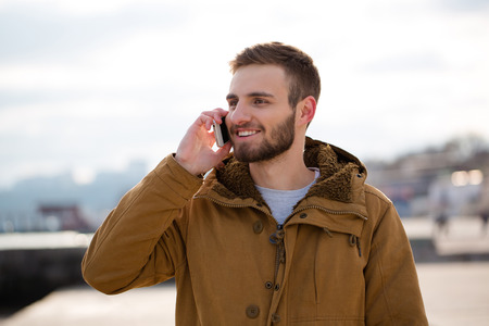 call of nature: Portrait of a smiling man talking on the phone outdoors