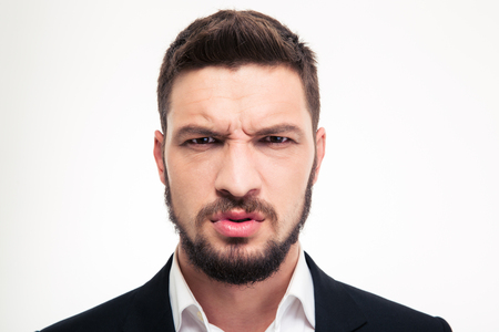 frowns: Close up of angry irritated bearded young business man in black suit and white shirt looking camera over white background
