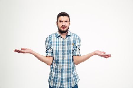Confused annoyed young man with beard in plaid shirt holding copyspace on palms over white background Stock Photo