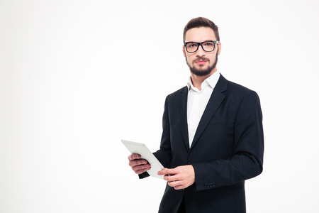 people working: Portrait of a serious businessman holding tablet computer and looking at camera isolated on a white background