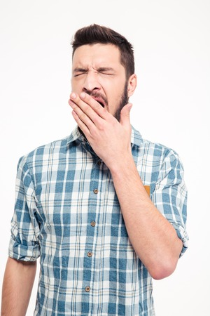slumberous: Tired exhausted bearded young man in checkered shirt standing and yawning Stock Photo