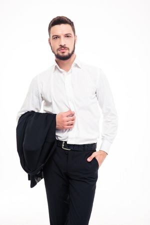 Handsome confident young businessman with beard in black siut and white shirt standing and holding jacket over white background Stock Photo