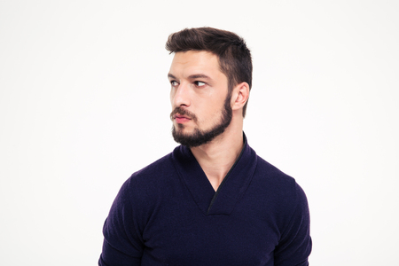 young style: Potrait of attractive thoughtful young man with beard in sweetshirt looking away over white background