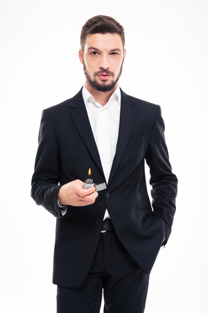 gas lighter: Confident bearded young business man in black suit and white shirt standing and holding gas lighter over white background