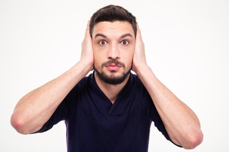 hands over ears: Portrait of dazed bearded young man closed ears by hands over white background Stock Photo