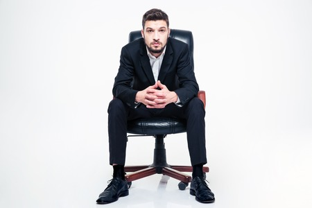 swivel chairs: Handsome young businessman with beard in black suit and white shirt sitting in black office chair over white background