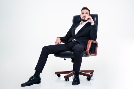 assured: Full lenght of assured confident young business man with beard in black suit sitting in office chair and looking camera over white background