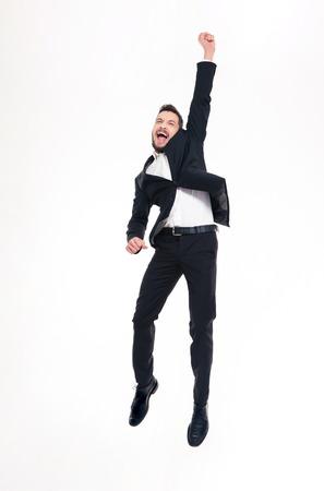 jumping: joven apuesto hombre de negocios excitado feliz con la barba en el clásico traje y zapatos de salto y celebra éxito sobre el fondo blanco