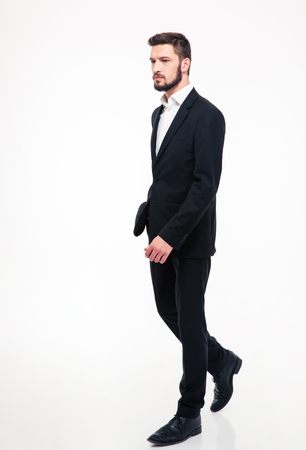 gente exitosa: Full length portrait of a handsome businessman walking isolated on a white background