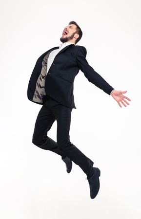 elated: Excited elated happy young business man with beard in classic suit jumping and shouting over white background