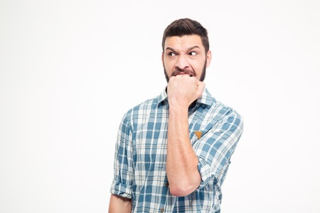 disappoint: Angry irritated aggressive young bearded man in plaid shirt biting his fist over white background