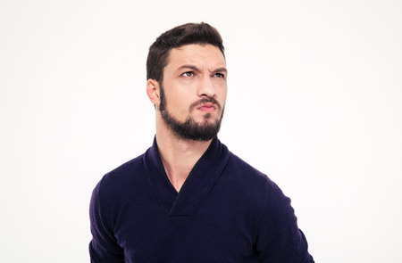Dissatisfied frowning handsome young man with beard in sweetshirt  looking away over white background Stock Photo