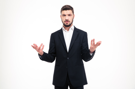 startled: Handsome puzzled young businessman with beard in black suit and white shirt holding copyspace in both hands over white background Stock Photo