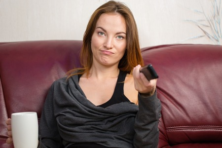 maroon leather: Annoyed beautiful young woman drinking tea and using tv remote control on couch in living room