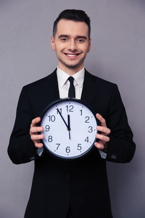 timekeeper: Portrait of a smiling businessman holding wall clock over gray background