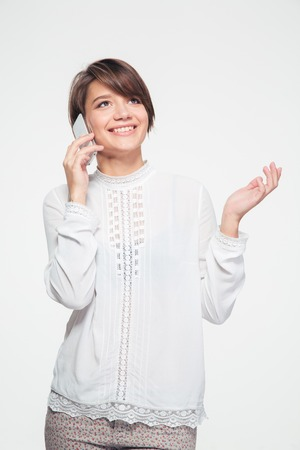 short haircut: Beautiful joyful young woman with short haircut standing and talking on cell phone over white background